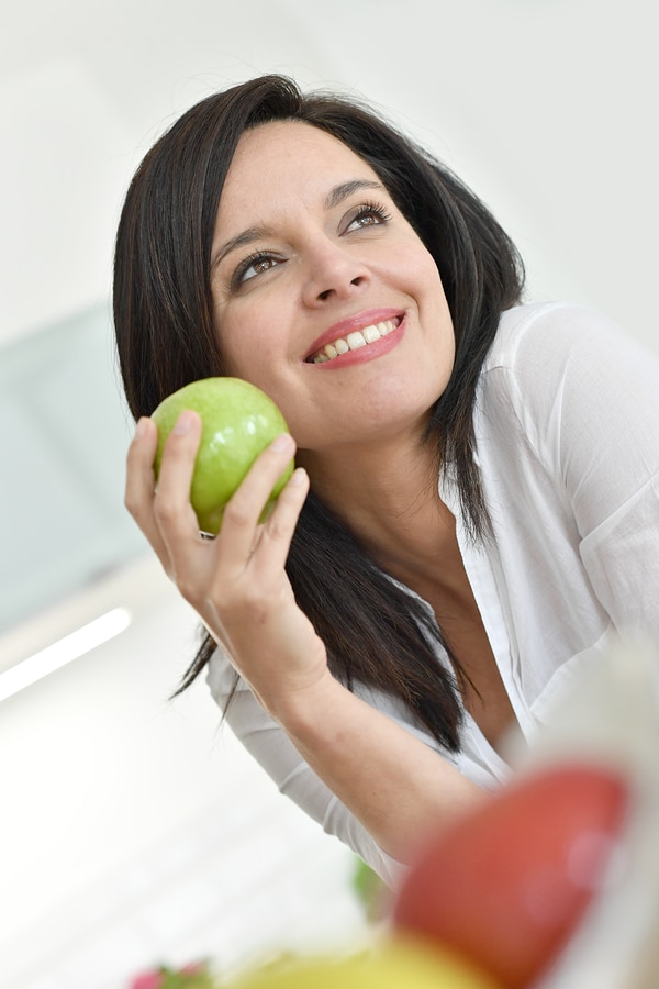 Beautiful mature woman eating green apple
